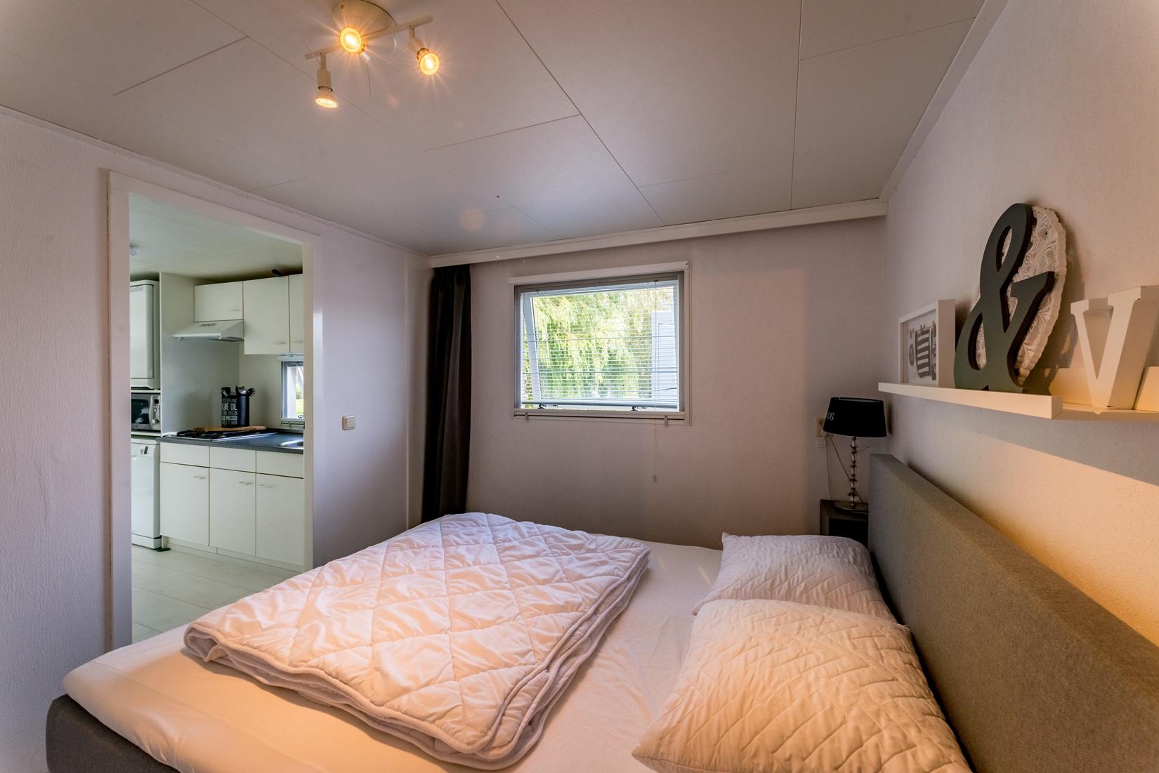 chalet-gestrand-interieur-master-bedroom--licht-doorkijk-keuken